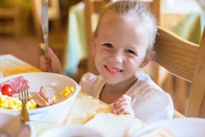 Adorable little girl having breakfast at resort restaurant